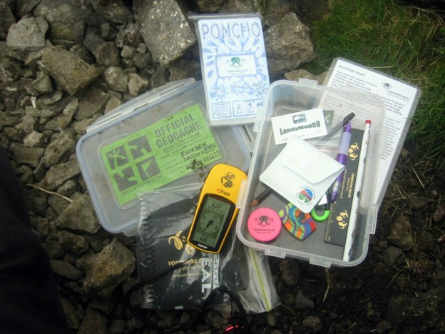 The contents of a geocache with a gps receiver at hand.